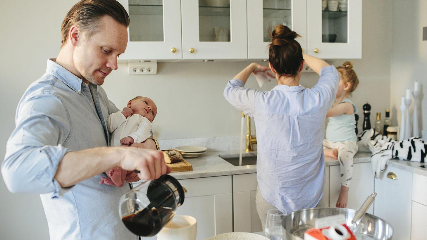 En familj i ett kök. Pappan bär på ett nyfött barn.